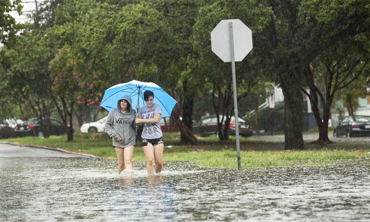 Rose Fennessey and Sarah Berry walk along a flooded road in Norfolk, Virginia, July 10, 2014, after a heavy rainstorm passed through the area. (AP Photo/The Virginian-Pilot, Bill Tiernan)