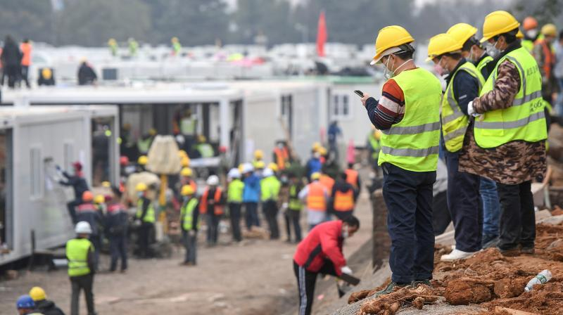 Chinese employees work at the construction site of the Huoshenshan hospital, which means