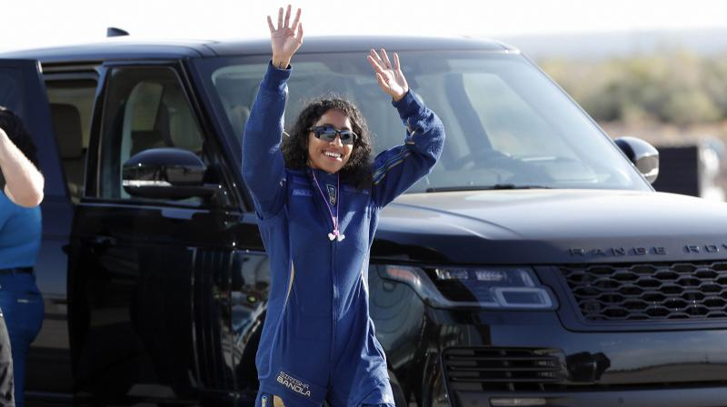 Sirisha Bandla, Virgin Galactic's Vice President of Government Affairs and Research Operations, and one of the passengers accompanying Richard Branson, waves to the crowd before heading to board the rocket plane that will fly them to space from Spaceport America near Truth or Consequences, New Mexico. (Photo: AP)