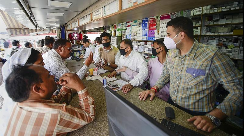 Salesmen at a chemist shop wear protective masks, in wake of the deadly novel coronavirus, outside Safdarjung Hospital, in New Delhi, Wednesday, March 4, 2020. (Photo   PTI)