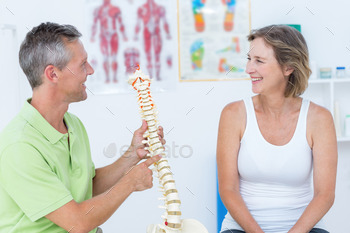 Doctor showing anatomical spine in medical office 491074