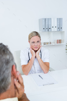 Doctor examining patient with neck ache in medical office 504606