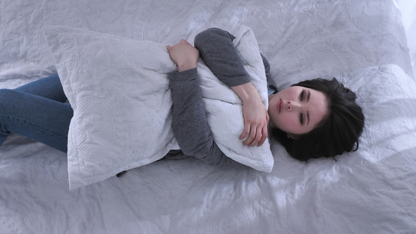 top shot young sad asian girl lying on the bed hugging a pillow unhappy
