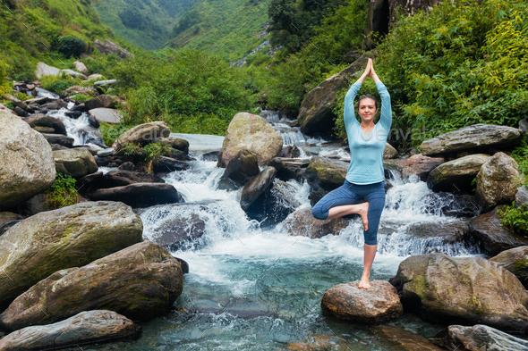 Woman in yoga asana Vrikshasana tree pose at waterfall outdoors Stock Photo  by f9photos