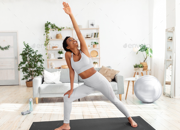 Fit black woman stretching her body on yoga mat during her home workout  Stock Photo by Prostock-studio