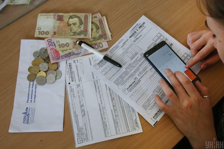 Дівчина рахує гроші та заповнює квитанції на оплату за житлово-комунальних та інших послуг, Київ, 17 червня 2016 року