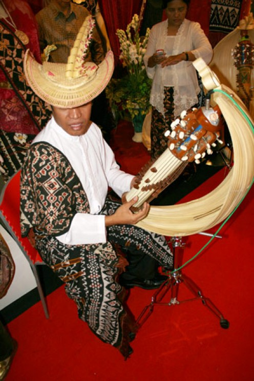 A man wearing Tiilangga (traditional hat) with Sasando beritadaerah.com