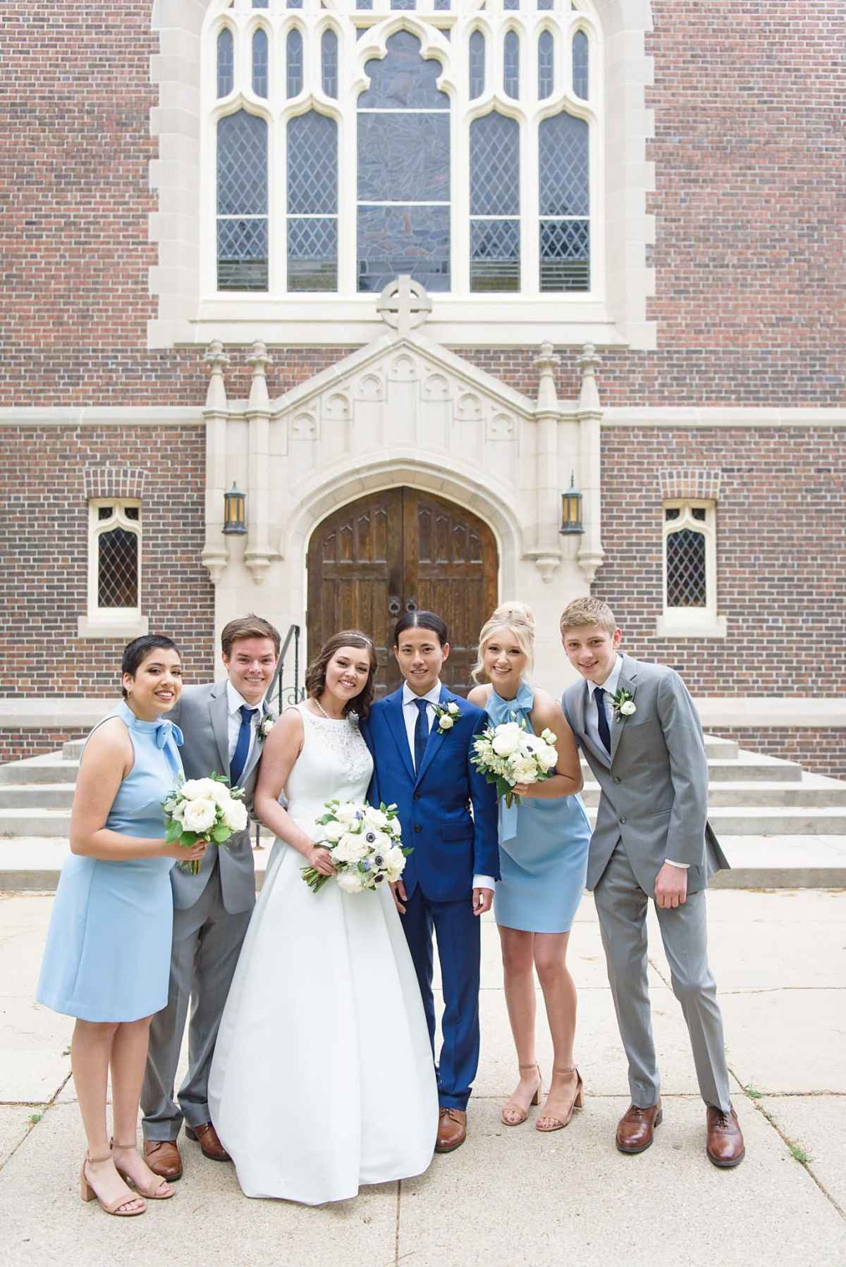 Bridal party celebrates with bride and groom in front of herrick chapel after grinnell college graduation in the morning, and a wedding in the afternoon.