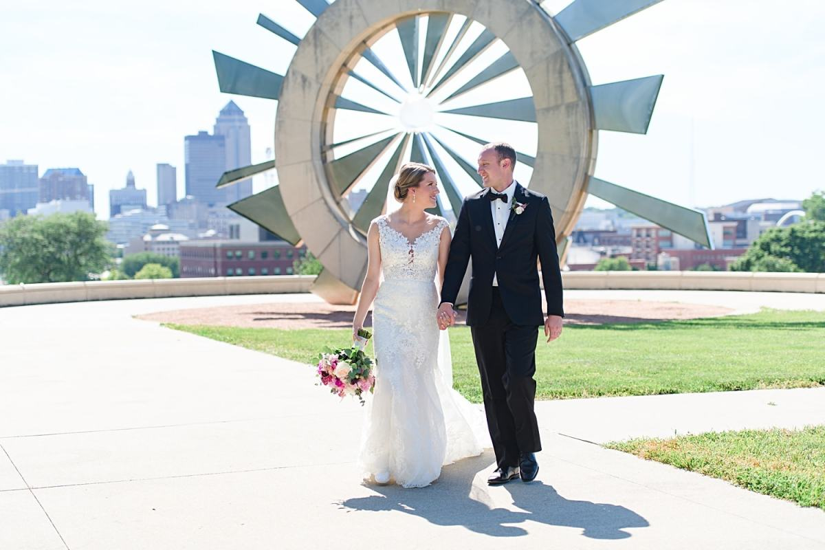 bride and groom walking by shattering silence monument in des moines