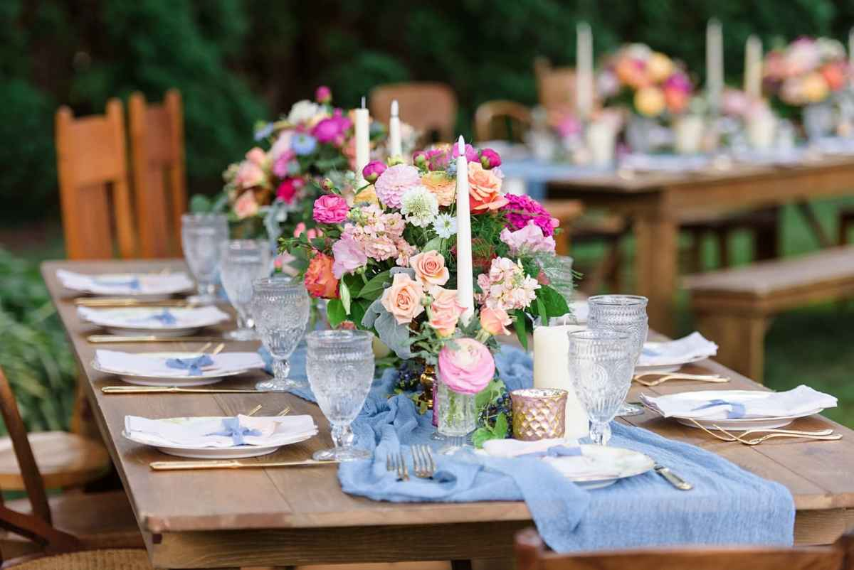 farmhouse table with wildflower floral centerpiece and tall candles