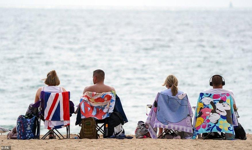 La gente se sienta en la tumbona y disfruta del clima en la playa de Bournemouth mientras la nación se prepara para disfrutar de temperaturas que alcanzan los 81 ° F