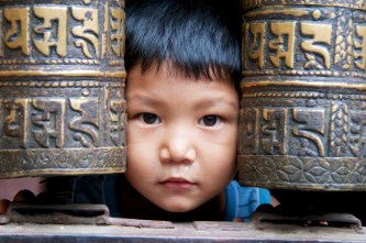 little-boy-with-face-between-prayer-wheels-kathmandu-nepal-copyright-2013-ralph-velasco