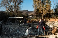 "Daphne is searching thought the debris of her family home with her daughter Claire, looking for any belongings that are in tact. The night the fires started she felt that this was more serious ""there have always been fires here and we have evacuated before, the winds where 85 miles an hour, it was a recipe for disaster - but I never assumed my home would burn down"""