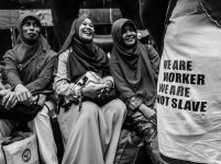 Three Indonesians migrant worker laugh with their friends while participating in a rally for worker rights in Hong Kong. September 03, 2017