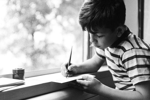 boy writing black and white photo