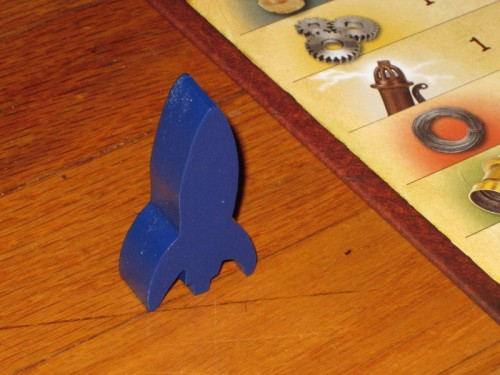 A blue rocket, the first-player marker for Mars Needs Mechanics