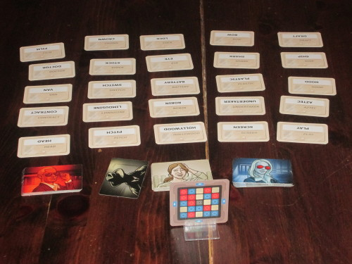 A game of Codenames set up. The key card indicates which agents belong to which spymaster's team, and the border around the card indicates who goes first. (That team has to guess an additional agent.)