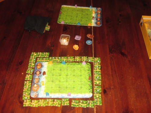Karuba set up for two players. All the adventurers and temples start out on the same position, and only one player's tiles is randomized.