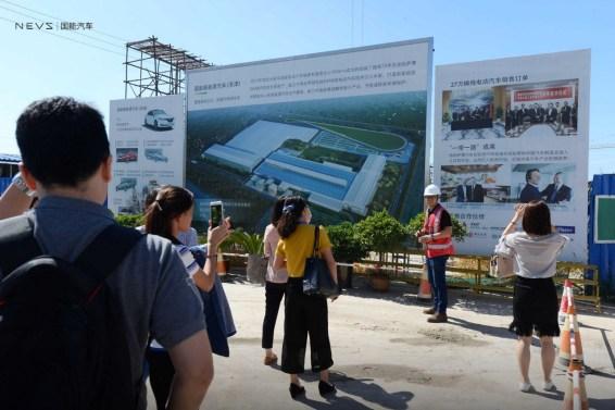 Besökargrupp framför fabriken. Foto Kredit: NEVS