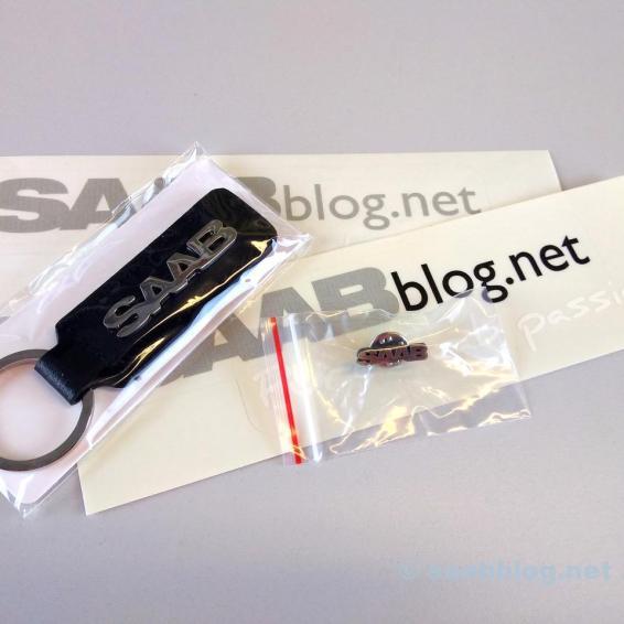 Ein Saab Schlüsselanhänger, ein Pin und Aufkleber sind ebenfalls im Paket