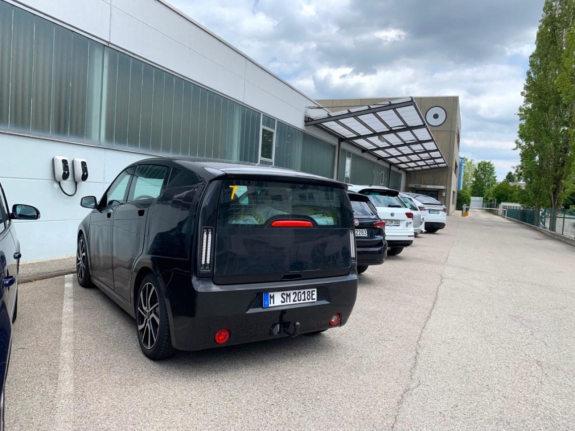 Соно Моторс в Мюнхене. На переднем плане Sion, логотип компании на заднем здании