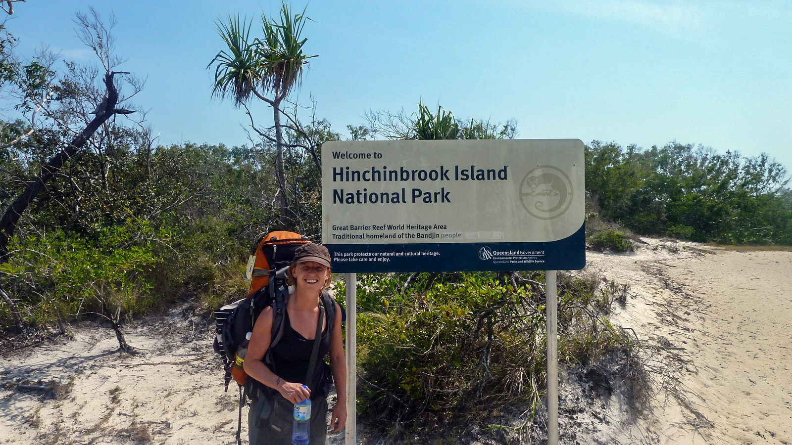 this is a photo of a hiker next to the sign showing the starting point of the hinchinbrook island trail