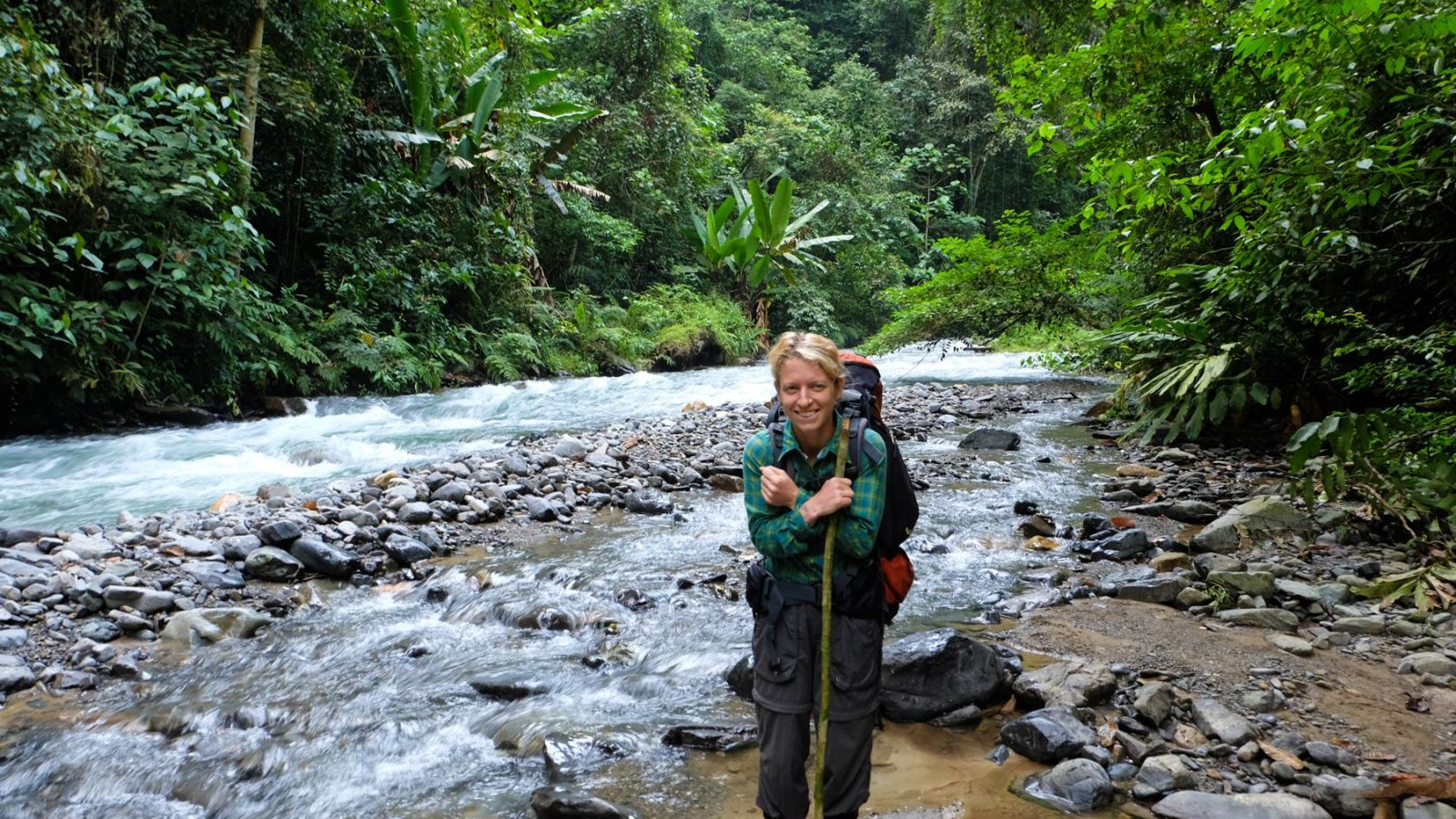 a photo of a hiker standing in a river in gunung leuser national park.