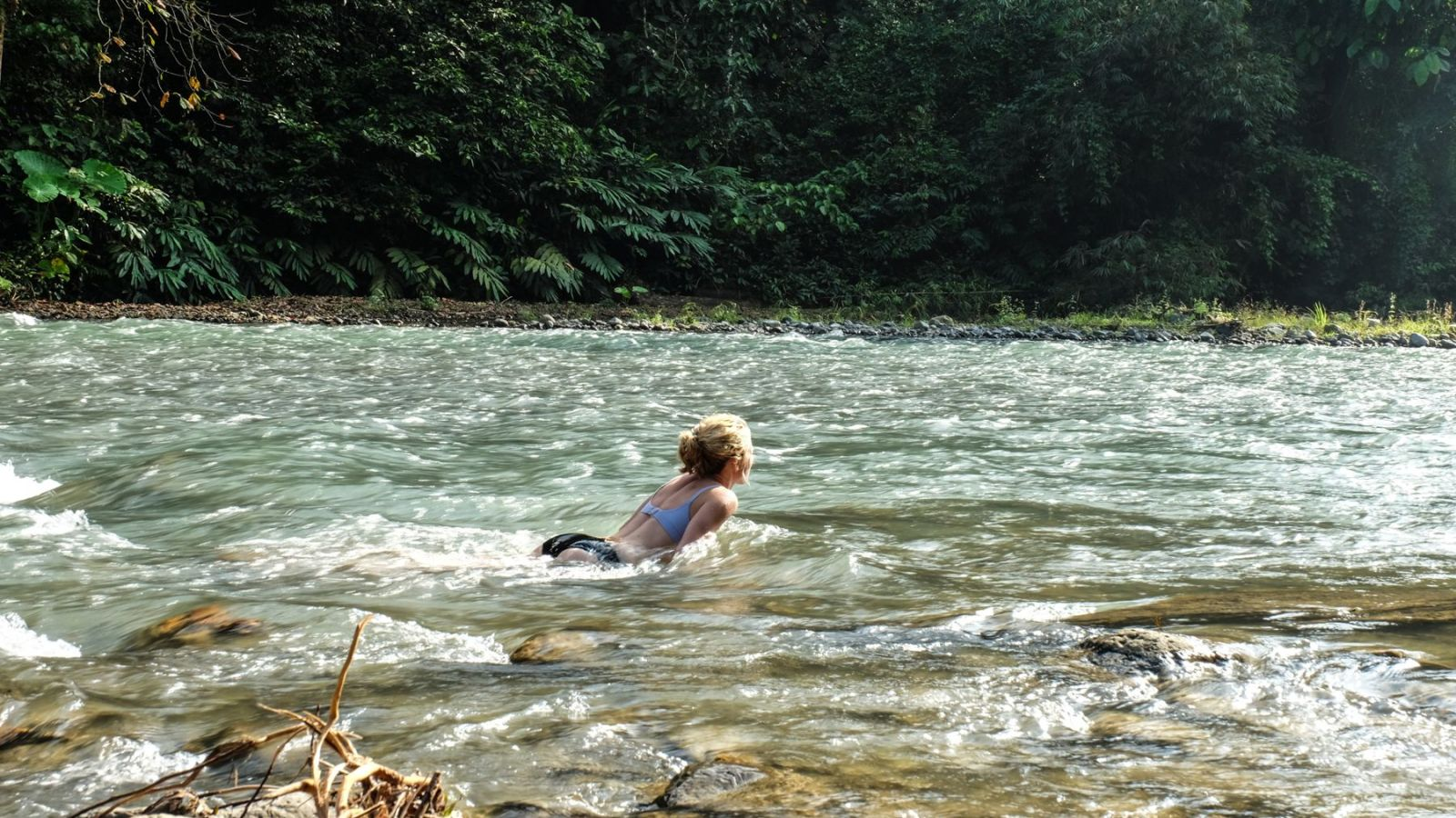 photo of a hiker taking a bath in a river in gunung leuser national park