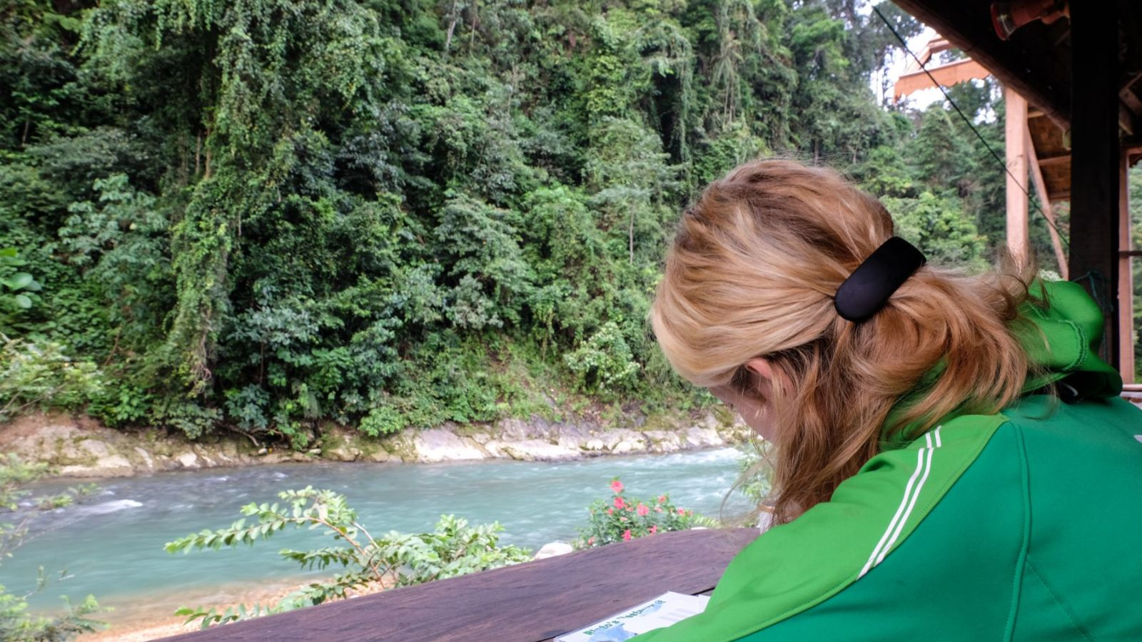 a photo of a person in a restaurant in bukit lawang with a river in the background.