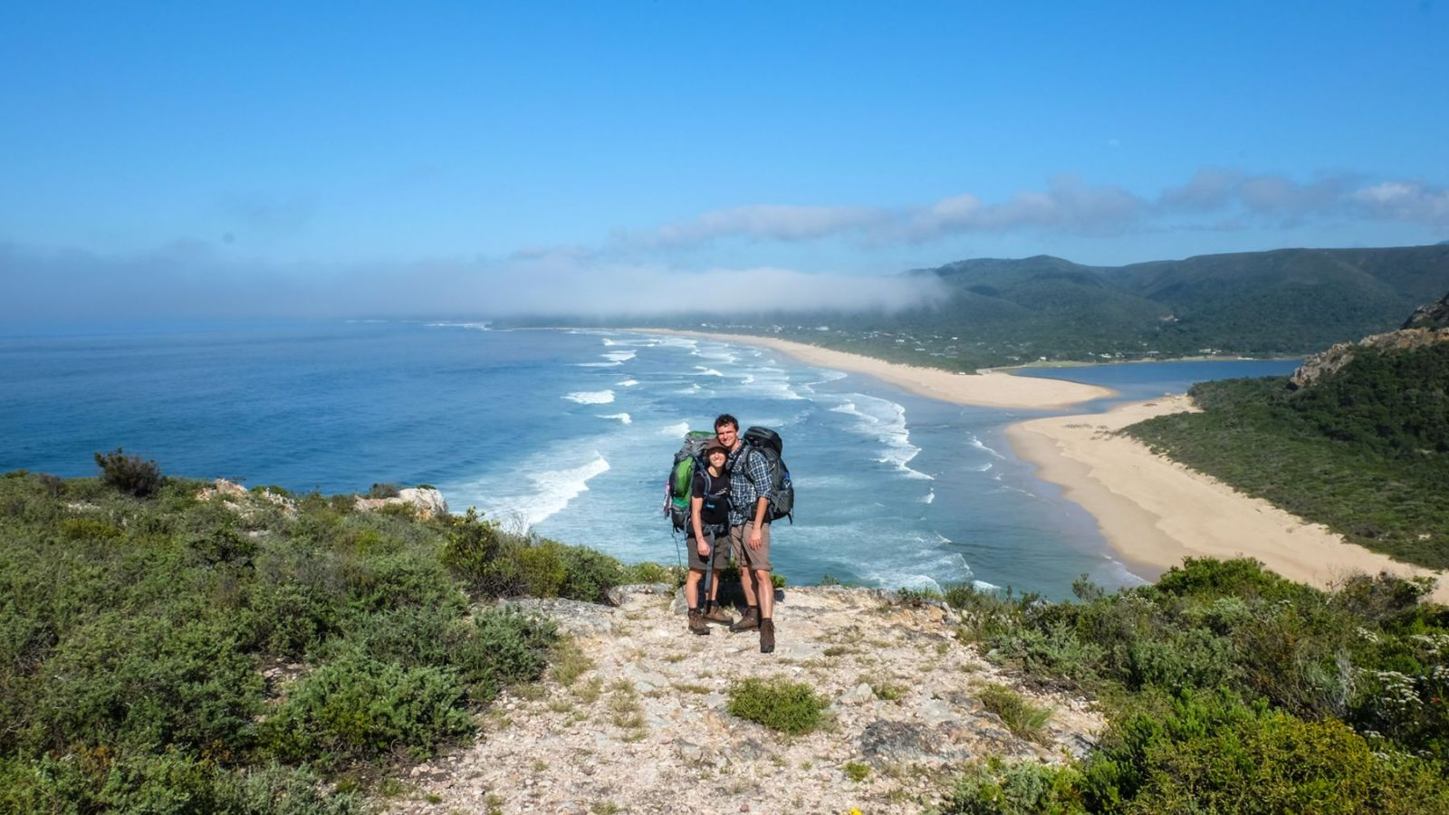 a photo of two hikers at the end of the otter trail with the coast in the background.