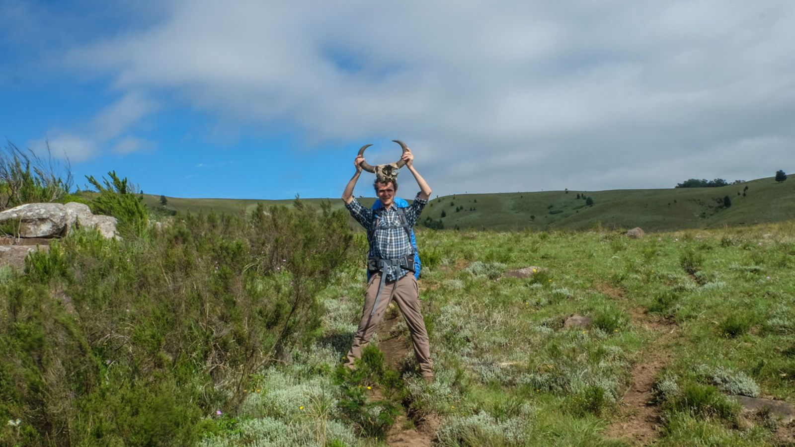 a photo of a hiker holding up deer antlers on the amathole trail.