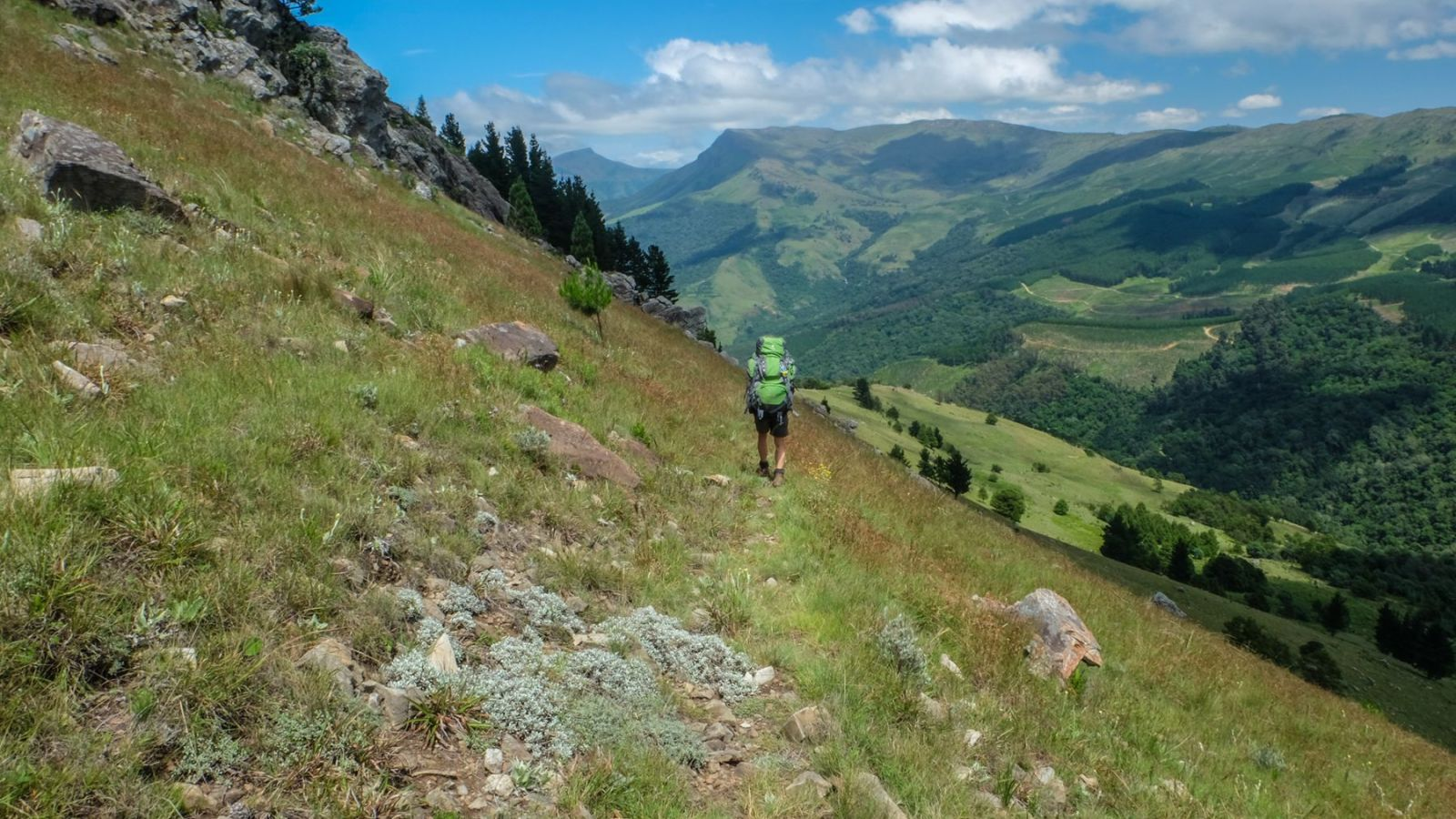 a photo of a hiker on the amathole trail with mountains in the background.