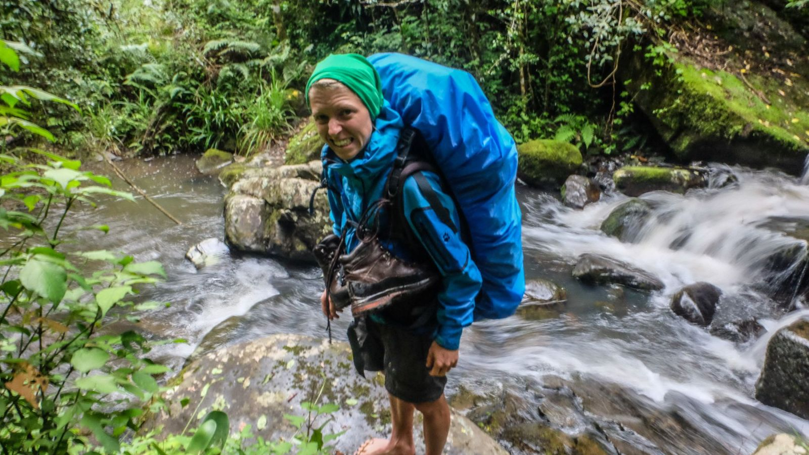 a photo of a hiker crossing a river on the amathole trail.