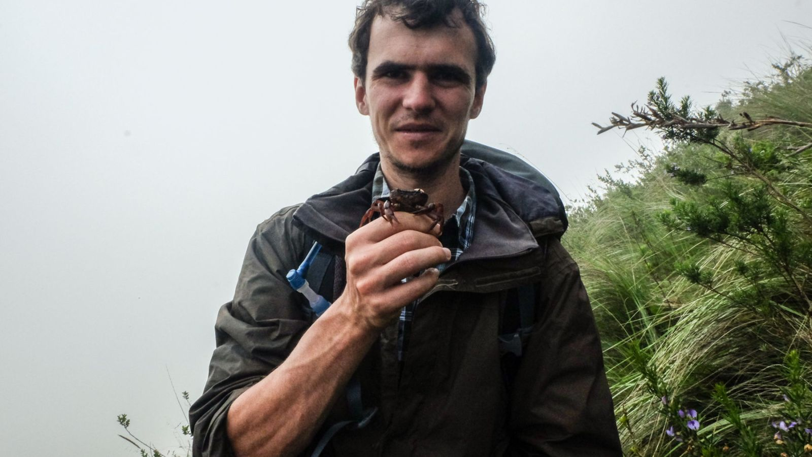 a photo of a hiker holding up a crab on the amathole trail in south africa.