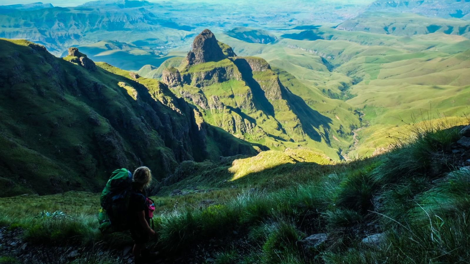 photo of the valley from the mountain plateau in the drakensberg mountains with hiker in the foreground