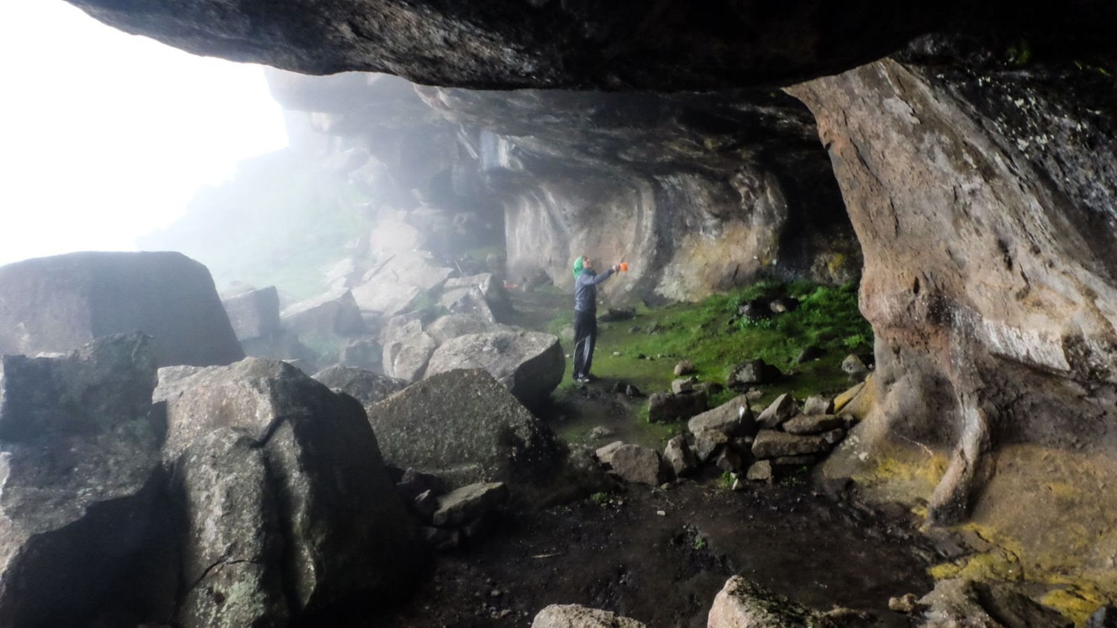 photo of a cave in the drakensberg mountains and a hiker collecting water