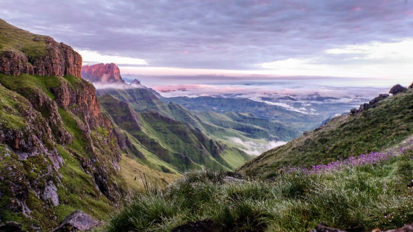 photo of a green valley in the drakensberg mountains during sunset