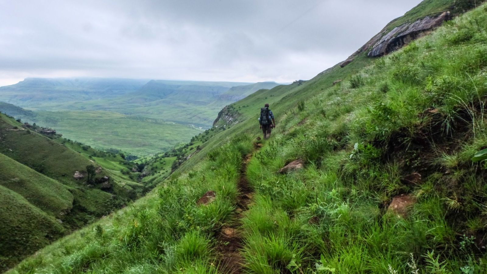 photo of a green valley in the drakensberg mountains with hiker in the distance