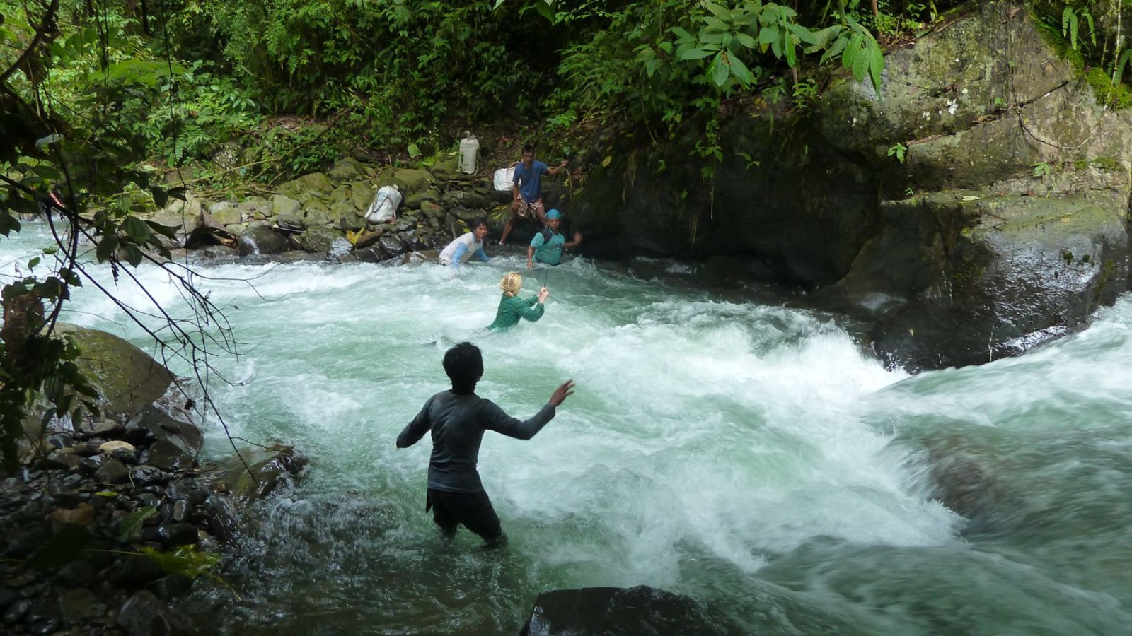 image of a hiker in gunung leuser national park crossing a river on a rope.