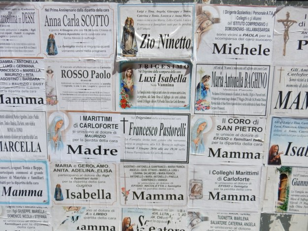 Death remembrances are posted on boards in Carloforte.