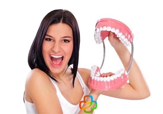 Mujer con una maqueta de prótesis dental