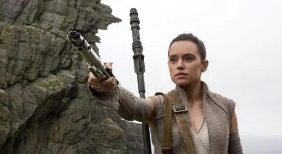 Rey handing a lightsaber toward Luke Skywalker