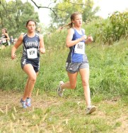 Senior Skylar McAfee keeps up with this St. Marys runner during the girls' cross country race on Thursday, October 4, at the Sabetha Golf and Country Club.