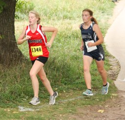 Madisen Cochran stays close to this Wamego runner during the girls' cross country race on Thursday, October 4, at the Sabetha Golf and Country Club.