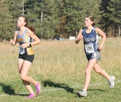 Sophomore Kenzie Meyer looks to pass this runner during the 3A State Meet on Saturday, October 27, at Rim Rock.