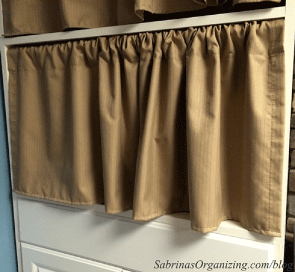 Put a curtain in front of a cabinet to hide items.