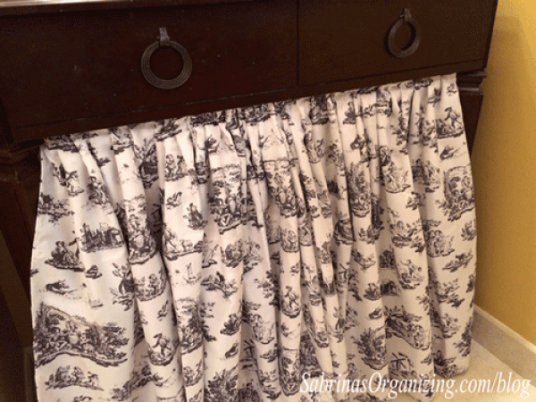 Add a curtain in front of a vanity to hide a basket and trash can