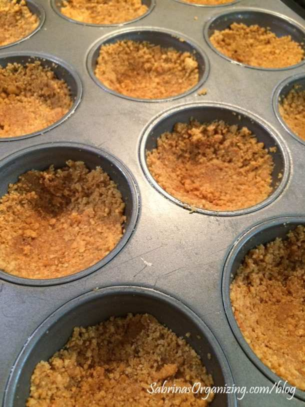 add graham cracker mixture to the muffin tin and press it down and to the sides