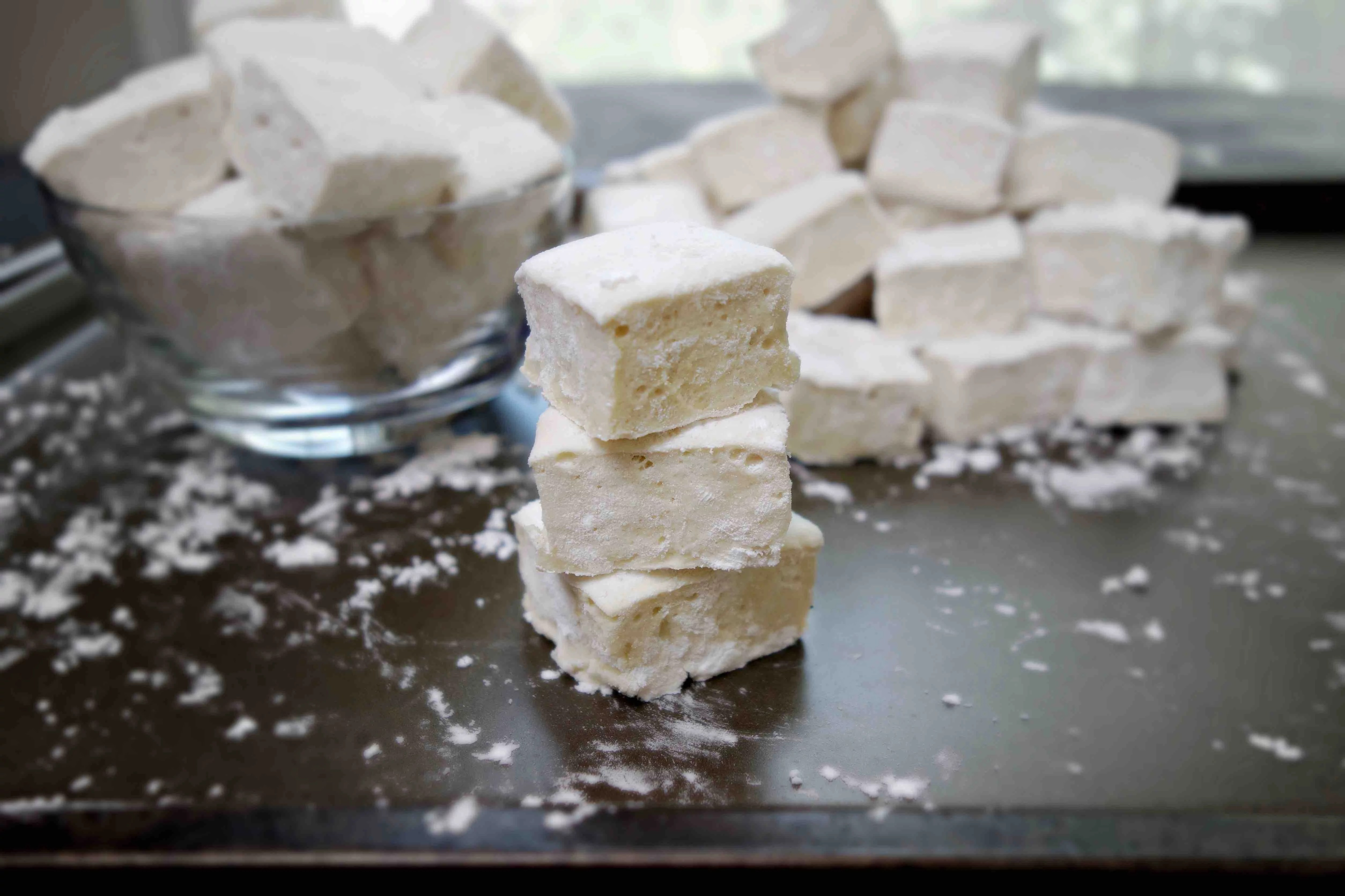 stacked homemade paleo marshmallows with more marshmallows in the background