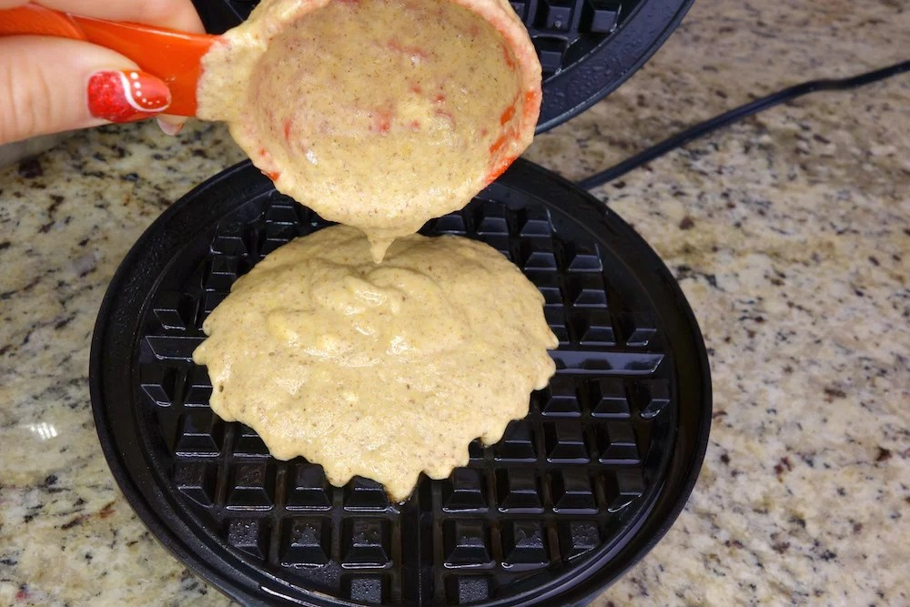 homemade Paleo pumpkin waffle batter being poured onto a hot waffle maker with a measuring cup